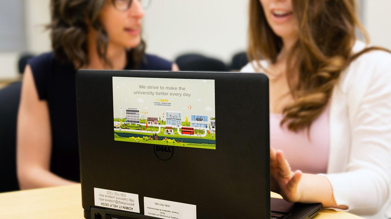 Photo of UC Davis workers using laptop with FOA sticker on it.