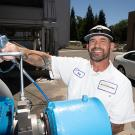 UC Davis employee in Facilities Management polo fills up a fuel tank. Car in background
